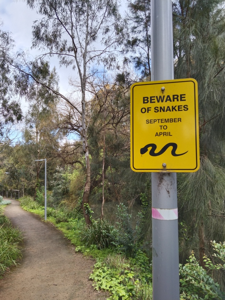 path with beware of snakes sign